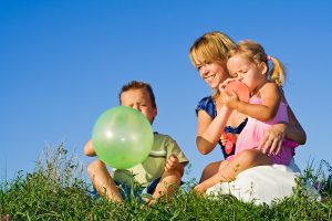 bigstockphoto_Woman_And_Kids_Playing_With_Ba_3476882